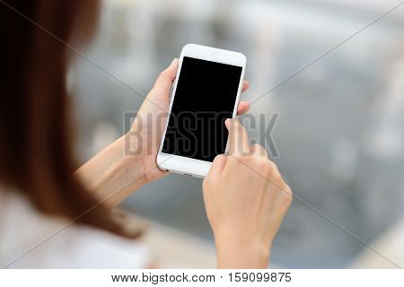 Woman's hand touching blank screen mobile smart phone outdoor.