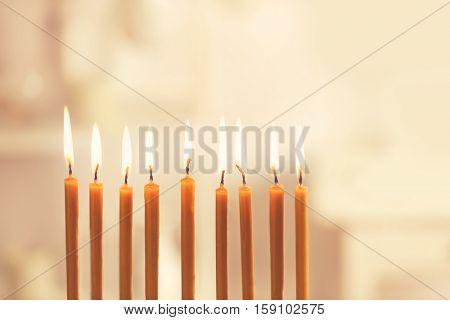 Nine burning candles on blurred background. Hanukkah concept