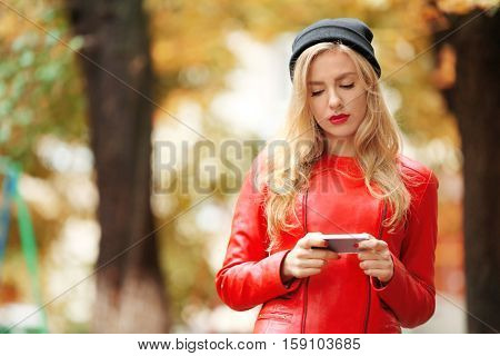 Young fashion woman with smart phone outdoors