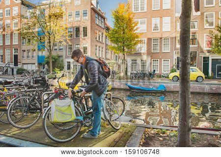Man in the Netherlands parking his bicycle at a narrow Amsterdam canal