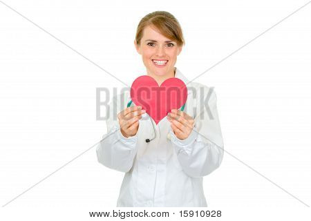 Smiling medical female doctor holding paper heart in hands isolated on white