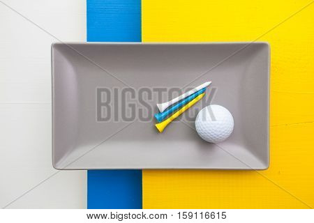 Gray ceramic dish with golf equipments on over white blue and yellow wooden table rectangle dish