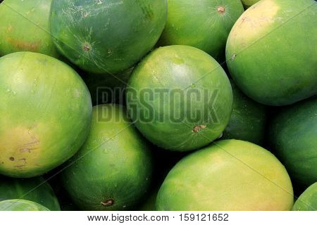 Horizontal image of several whole watermelons stacked together at local farmers market.