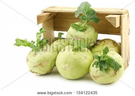 Freshly harvested kohlrabi with some foliage in a wooden crate on a white background