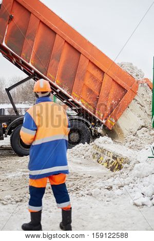 Worker watches at unloading of snow from truck into bunker for snow processing.