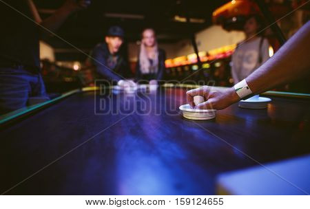 Young friends playing air hockey game at amusement park focus on hand of man holding striker.