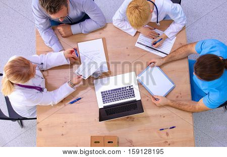 Male and female doctors working on reports in medical office.
