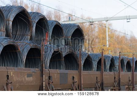 row of train cargo wagons with rolls of steel wire