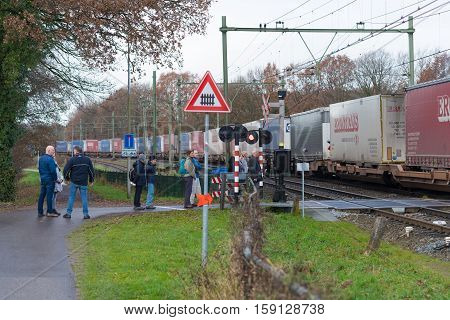 OLDENZAAL NETHERLANDS - NOVEMBER 27 2016: Unknown people waiting for a passing container train on a secured train crossing