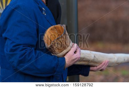 man holding the end of a traditional handmade horn in his hands. These horns a blown during the advent period in some eastern parts of the netherlands