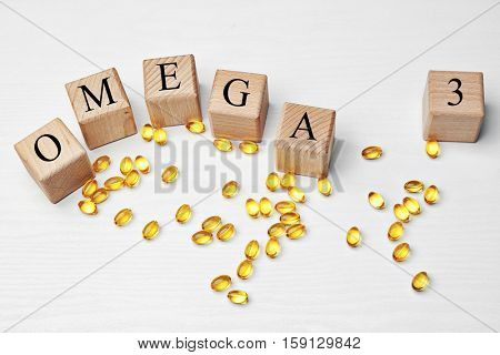 Fish oil pills and wooden cubes with inscription OMEGA 3 on light background