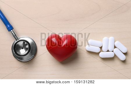 Red heart with stethoscope and pills on table