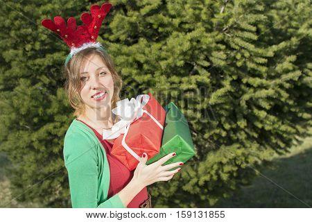 Beautiful  Girl With Reindeer Ears Holding Christmas Presents