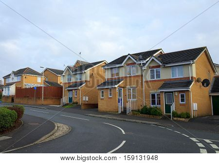 Bracknell,England - November 23, 2016: A row of brick built homes on a modern housing estate beside a road in Bracknell, England