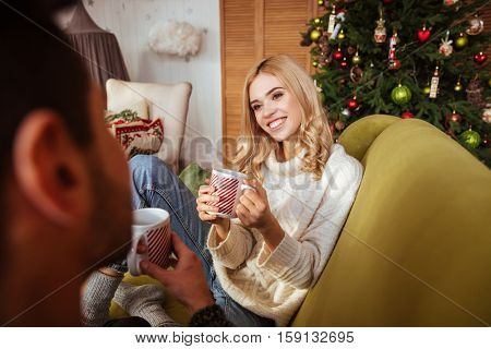 Photo of the girl made from behind man. couple sitting on sofa
