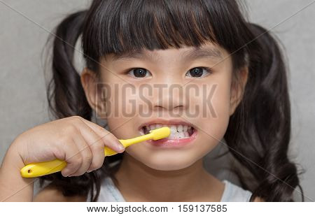 Little asian cute girl brush teeth .