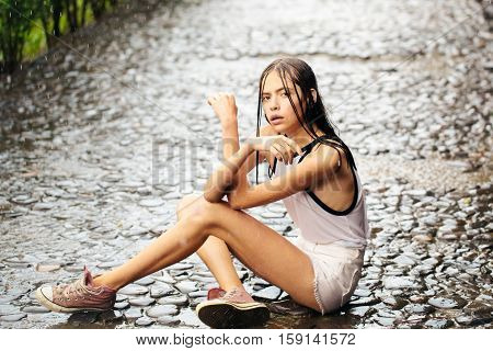 Pretty girl cute beautiful woman with wet hair and clothes sits on cobblestone road in water drops outdoors under summer rain