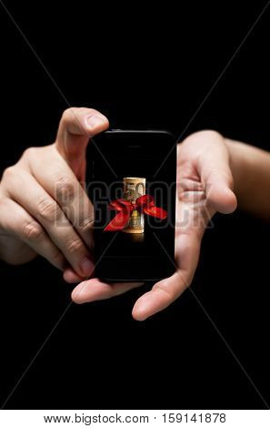 Hands Holding Smartphone showing Fifty Euro Bill with Red Ribbon as a gift (on black background with very shallow depth of field)