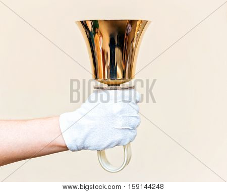 Jingle bells. Close-up of girl holding metal bell in hand and against light background