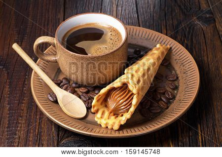 Cop of hot coffee and waffle cones with condensed milk in plate on old wooden table