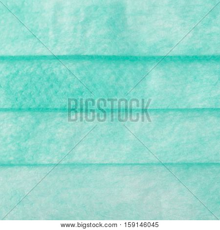 Green medical surgical flu illness protective mask texture as abstract background