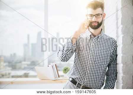 Close up portrait of cheerful handsome male in glasses talking on mobile phone. Communication concept