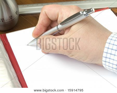 Hand Holding A Pen And Sheet Of A Paper Laying On A Desk