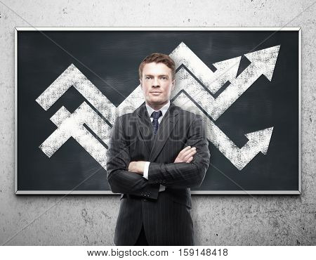 Handsome young businessman with chart arrows on blackboard. Financial growth concept