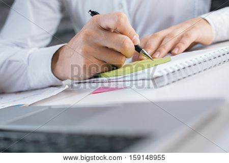Close up of male hand writing in notepad with green stickers
