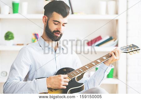 Young man at workplace playing the guitar