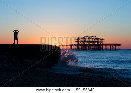 Person practicing Tai Chi at sunrise near West Pier Brighton.
