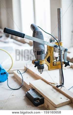 Screw and electric drill on wood at workshop.