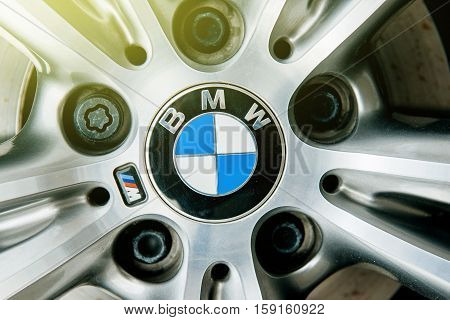 MUNCHEN GERMANY - APRIL 06 2015: BMW electric limousine alloy wheel detail with logotype of BMW on it and sun flare