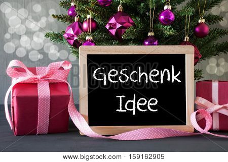 Chalkboard With German Text Geschenk Idee Means Gift Idea. Christmas Tree With Rose Quartz Balls And Bokeh Effect. Gifts Or Presents In The Front Of Cement Background.
