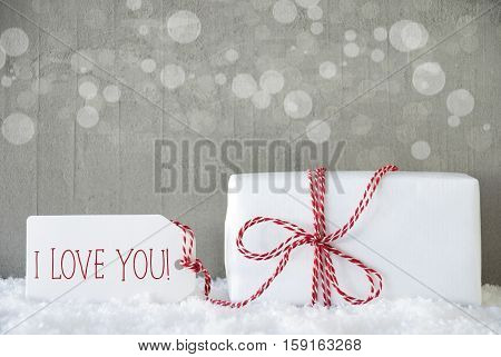 One Christmas Gift Or Present On Snow. Cement Wall As Background With Bokeh. Modern And Urban Style. Card For Birthday Or Seasons Greetings. Label With English Text I Love You