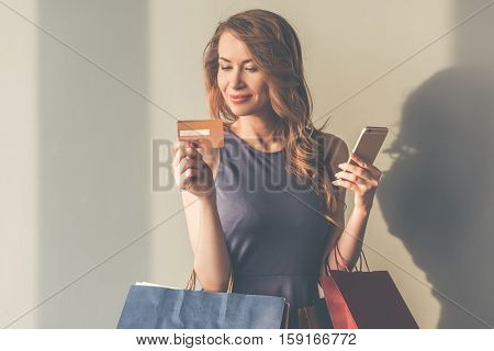 Beautiful stylish young woman in cocktail dress is holding shopping bags smartphone and a credit card and smiling on gray background