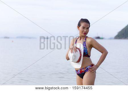 Bikini with women shape beautiful hat and sunglasses on Thung Wua Lan Beach at Chumphon Province Thailand