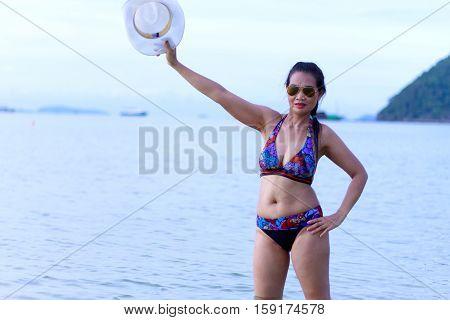 Bikini with women body beautiful hat and sunglasses on Thung Wua Lan Beach at Chumphon Province Thailand