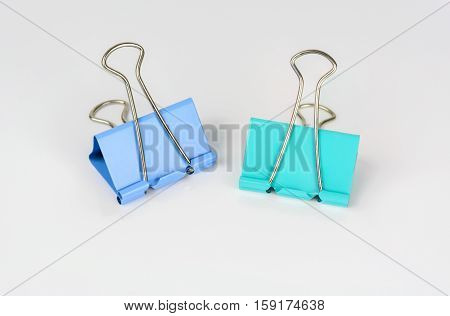 Blue and green paper clip isolated on white background.
