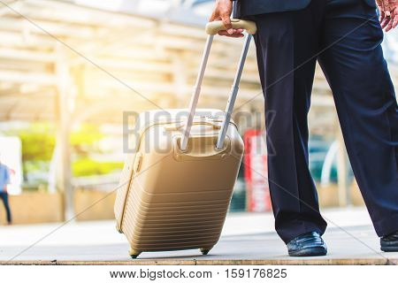 Business Man Hold A Luggage Case And Walk In The City. Business Trip. Business  In The City Concept.