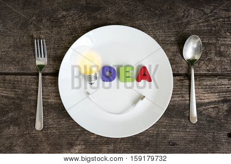 Big light bulb idea glowing with smile usb charge cable on a plate with spoon and fork on grungy table Unique and Creative thinking concept