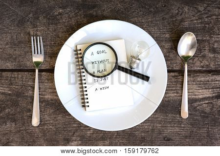 a goal without a plan is just a wish motivational handwriting on a open notebook with magnifying glass and light bulb in a plate with spoon and fork on grunge table