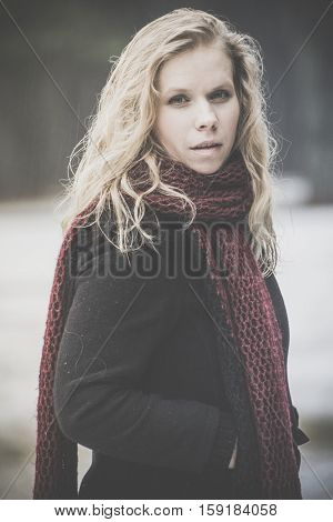 portrait of blond woman with blue eyes on dark background winter girl in black coat, curly hair, blond and beautiful covered with light snow, penetrating eyes, resolute and stern, the photo on street