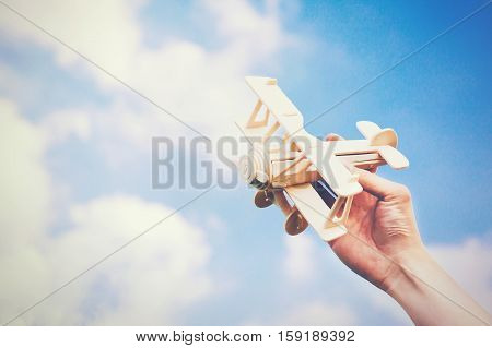 Human Hands Holding A Wooden Plane Toy Over Blue Sky With Copyspace