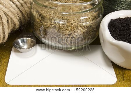 Seeds of cumin usual and black with a rope and a card on the table