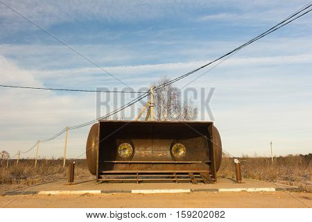 Rural bus stop shelter from iron in a robot shape. Russia
