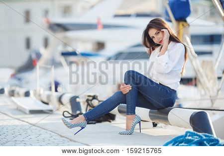 Slim beautiful brunette woman with thick long hair and brown eyes,light makeup and red lipstick in my ears,wears large gold earrings,dressed in a white shirt  and blue jeans,posing in the summer near the sea on blurred background of yachts