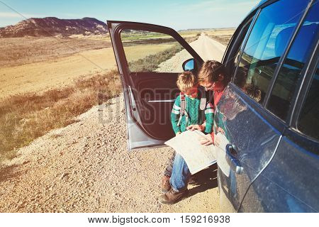 father and son looking at map while travel by car, family travel