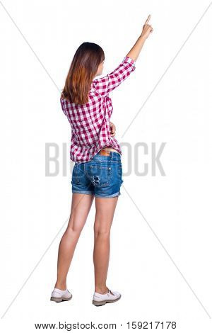 Back view of  pointing woman. beautiful girl. Rear view people collection.  backside view of person.  Isolated over white background. Girl in shorts and checkered shirt shows a hand up.