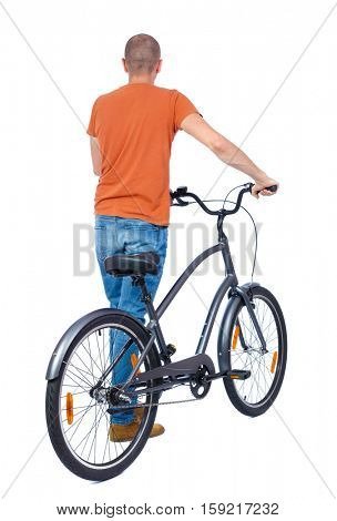 back view of a man with a bicycle. Cyclist keeps the wheel of a bicycle. Rear view people collection.  backside view of person. Isolated over white background. The guy in a T-shirt is a bicycle.
